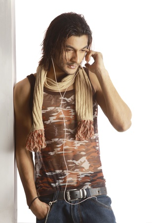 Image of a handsome young male wearing sleeveless and scarf, listening music with hands in pockets standing against white background. photo