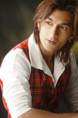 long shot: Chiudere l'immagine di un maschio attraente giovane con lunghi capelli castani che indossa abbigliamento casual e guarda lontano.
