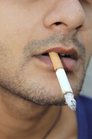 smoking a cigarette: Close-up shot of a guy with cigarette in his mouth