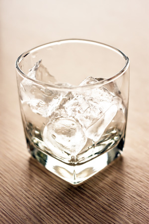 ices: Glasses with ice cubes on wooden table. Stock Photo