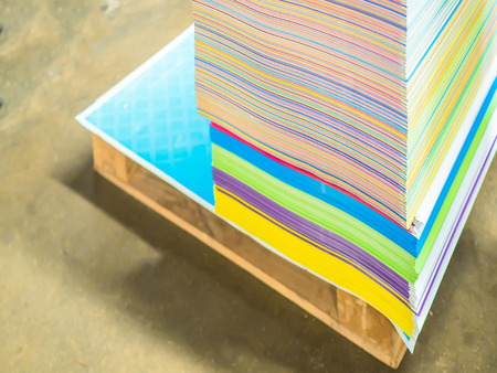 paper factory: pile of papers in difference colors ready to make a books in paper factory. Stock Photo