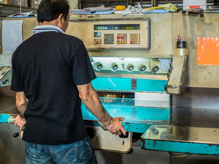 lithograph: Asian man uesing paper cutter to make books in factory. Stock Photo