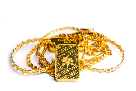 Gold biscuit bar, chains, ornaments on a white background.