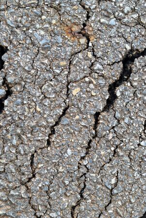 closeup of cracks on asphalt road photo