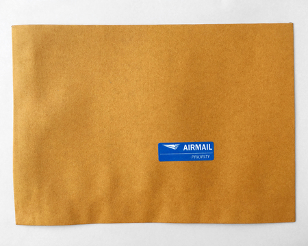 airmail priority sticker on brown paper. Stock Photo