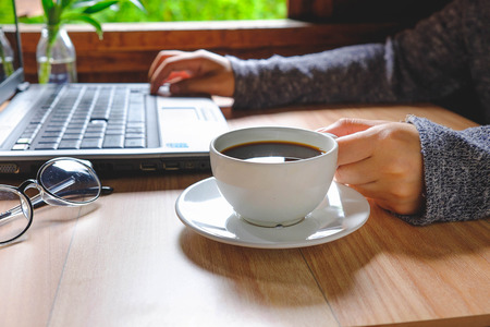 A cup of coffee on a woman's work table.