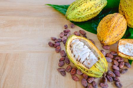 Fond de fruits de cacao avec des cabosses de cacao et des fèves de cacao sur table en bois Banque d'images