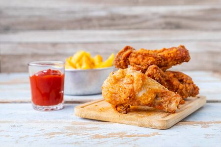 Fried chicken food and french fries on a wooden table