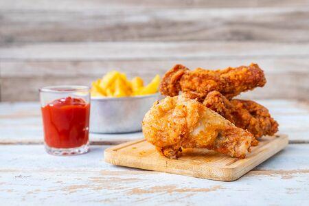 Gebakken kip eten en frietjes op een houten tafel