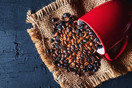 Roasted coffee beans in a red coffee cup on a wooden table Фото со стока