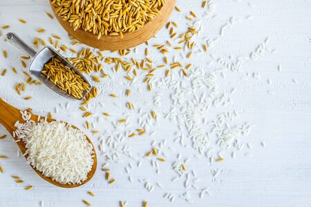 Organic white  rice and paddy on a wooden table Imagens - 146612512