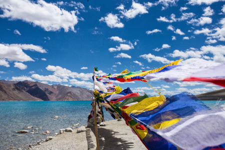 rock bottom: Pangong lake with blue sky and Buddhist prayer flags