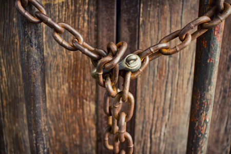 keep gate closed: Rusty chains and padlocks on a fragile wooden door.
