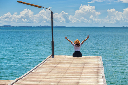 Asian woman sitting happy on the Wooden bridge looking at the sea at Khao Laem Ya Mu Ko Samet National Park , Rayong , Thailand