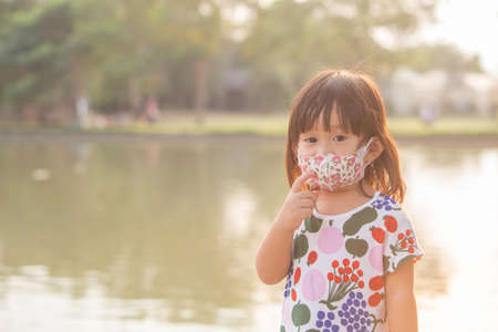 A girl wears a mask with a cartoon character for protect pm2.5 and protect virus at the park