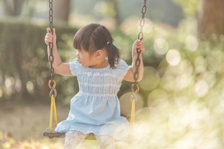 Little girl having to play swing first time in the playground , the evening