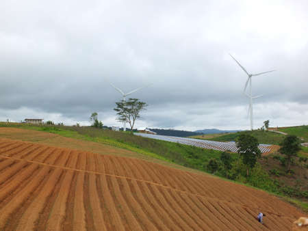 Preparing the soil for cultivation on a hill, with wind turbines and clouds in the sky behind.