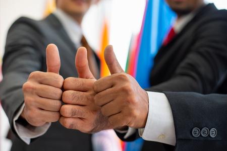 Daumen hoch von Geschäftsmann oder Politiker während der internationalen Konferenz Standard-Bild