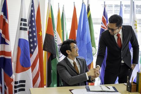 Ein paar Geschäftsleute oder Politiker sehen glücklich aus und geben sich die Hand, um die Zusammenarbeit ihrer Arbeit während der internationalen Konferenz zu zeigen