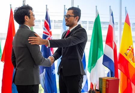 Ein paar Geschäftsleute oder Politiker sehen glücklich aus und geben sich die Hand, um die Zusammenarbeit ihrer Arbeit während der internationalen Konferenz zu zeigen Standard-Bild