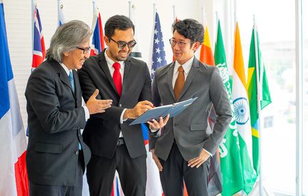 Eine Gruppe von Geschäftsleuten oder Politikern sieht während der Diskussion über ihre Arbeit glücklich aus und steht vor verschiedenen internationalen Flaggen Standard-Bild