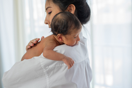Asian mother with white shirt place upon the shoulder of little newborn baby after give milk and the baby look sleepy Imagens