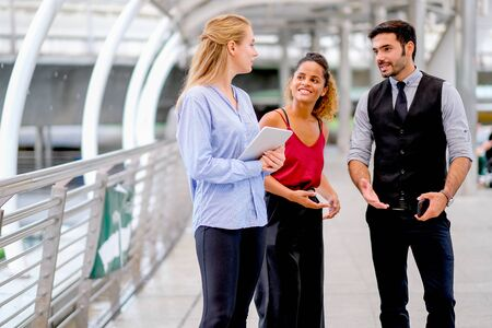 One business man discuss about work with his team, two women with one mixed race tan skin and white Caucasian woman who holds tablet.