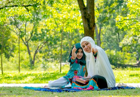 Muslim woman point to camera and girl show thumps up action during reading some books in the garden.