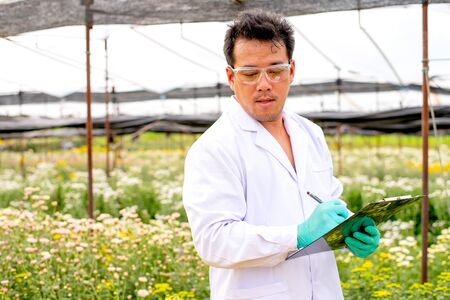 Asian scientist man with white lab gown analysis and record the data of white and multicolor flowers in the garden during day time. Stock fotó