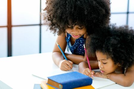 African girls as older and younger sister write or draw something on white paper near the book in front of glass windows with day light.