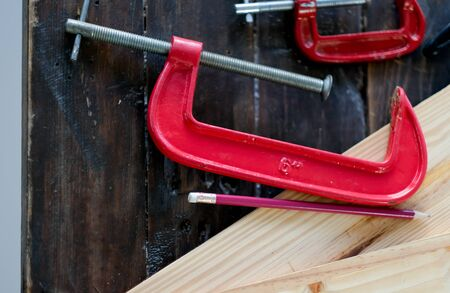 Close up view of red clamp tool for wood crafting work that is put on wood table with pencil and the other equipment.