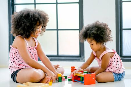 Two young African girls play toys together with main focus on right side girl who look concentrate with her toys. Banque d'images