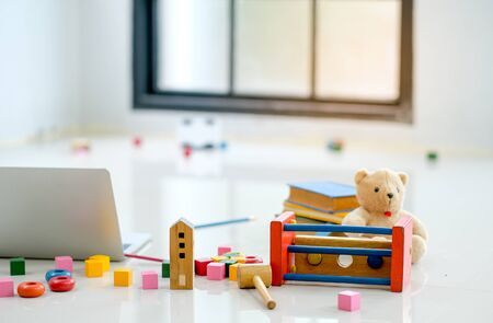 Various types of toys and doll are put on the floor near to laptop computer in front of glass windows.