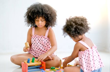 Two young African girls play toys together with main focus on left side girl who look concentrate with her toys.