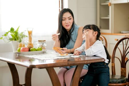 Asian little girl enjoy with bread eating and sit near her mother in the kitchen with fruit on the table. Main focus is little girl who eat bread. Stock Photo