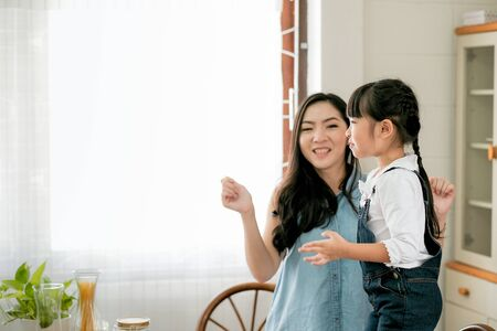 Asian little girl dance with her mother in the kitchen in the morning and she look to the window with happy emotion.