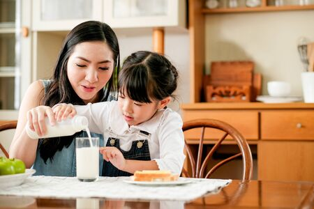 Asian mother take care her daughter pour milk to a glass on the table in house kitchen during breakfast meal. Main focus is the mother.