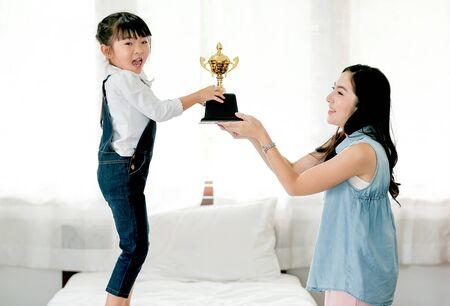Asiatische Tochter drückt aufregend aus, nachdem sie von ihrer Mutter eine Belohnung als Trophäe bekommen hat und sie auf einem weißen Bett steht.