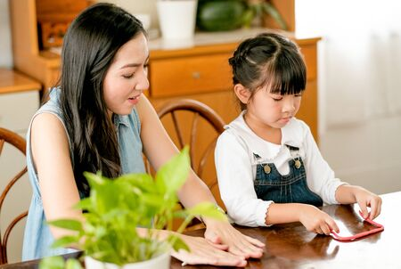Asian mother and daughter play together with clay in the kitchen and they look happy. Stock Photo