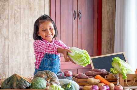 Soft blur image of Asian little young girl hold green lettuce and smile among various types of vegetable on the table in her kitchen with concept happiness with cooking and organic food.