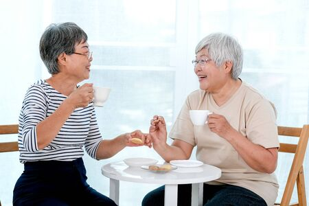 Two Asian elderly women drink tea together in the morning and also have some cookies, they are smile and talk about happy stories.