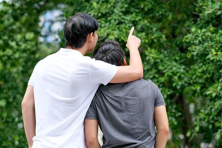 Asian gay couple stay on balcony and one point to make attractive to the other in front of green tree background.