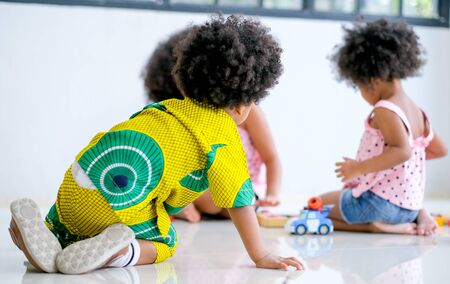 One African boy look at two girls play toys together and look like he want to play with them.