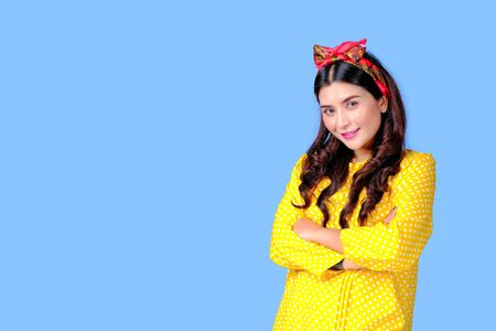 Beautiful woman with red headband and yellow dress act fold over in front of blue background, also with concept of retro image.