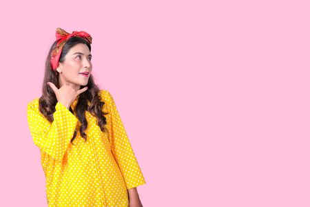 Beautiful woman with red headband and yellow dress act as phone call in front of pink background, also with concept of retro image.