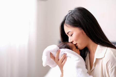 Camisa blanca Madre asiática besa en la frente de su bebé recién nacido en el dormitorio frente a ventanas de vidrio con cortina blanca para mostrar amor y unión familiar.