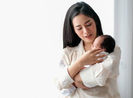 Beautiful Asian mother talk to her newborn baby in front of white curtain with day light. Stock fotó