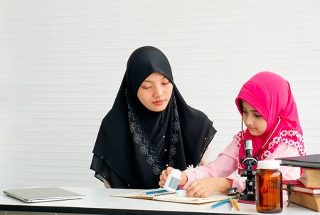 Muslim mother teach her daughter to learn about science and health in the room with white curtain.