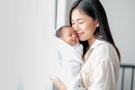 White shirt Asian mother is kissing her newborn baby in bedroom in front of glass windows with white curtain to show love and family bonding.