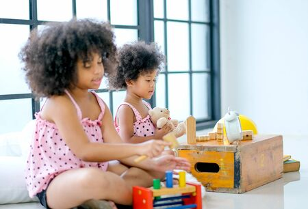 Two young African girls play toys together with main focus on front girl who look enjoy with her toys.